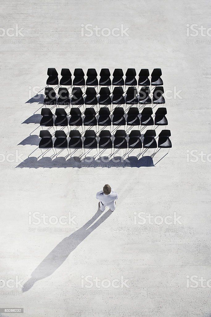 Businessman looking at lines of empty office chairs royalty-free stock photo