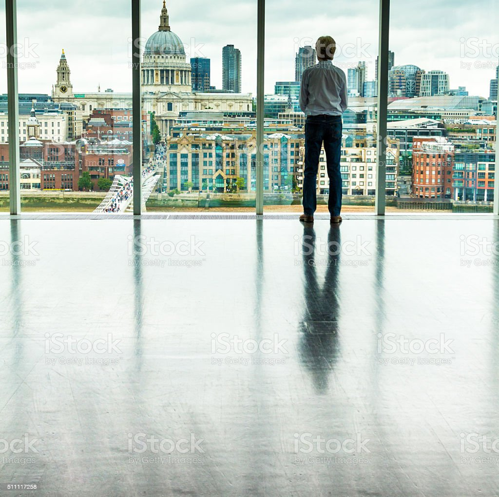 Businessman Looking at London City Skyline from Office Window stock photo