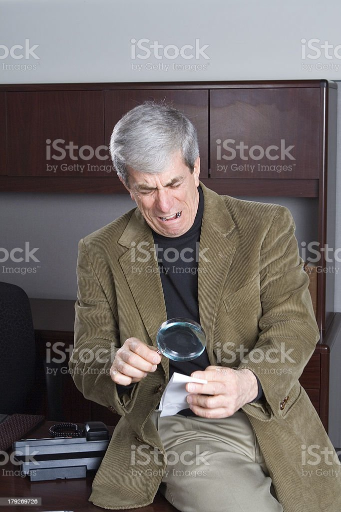 Businessman Looking at Paper with Magnifying Glass Shock and Disgust royalty-free stock photo