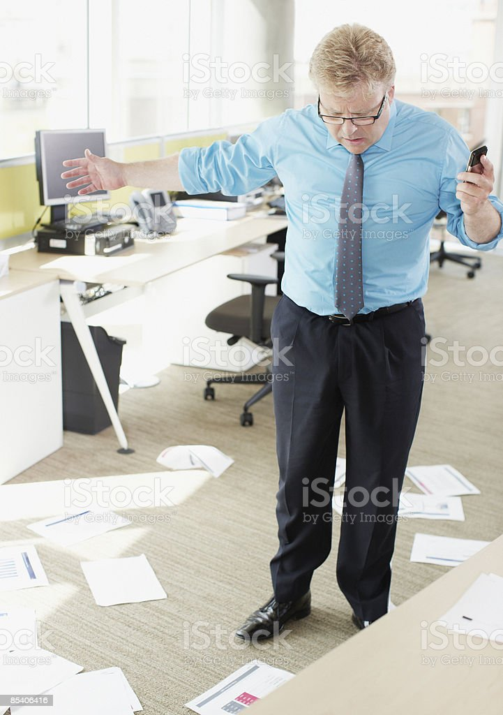 Businessman looking at papers on floor royalty-free stock photo