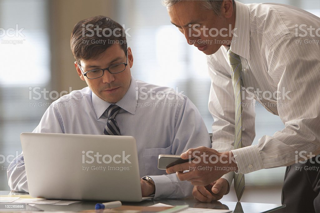 Businessman looking at report on laptop royalty-free stock photo