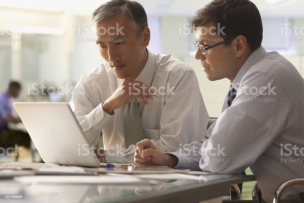 Businessman looking at report on laptop stock photo