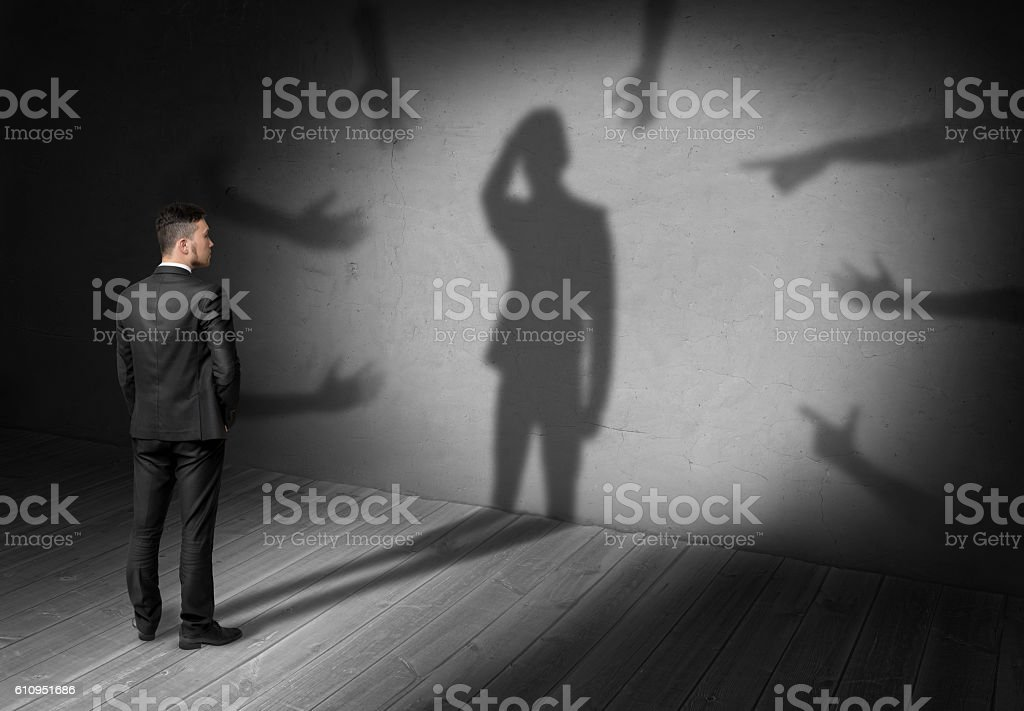 Businessman looking at shadow where many hands reach for him stock photo