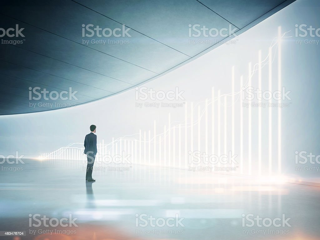 Businessman looking at shining chart on the wall stock photo