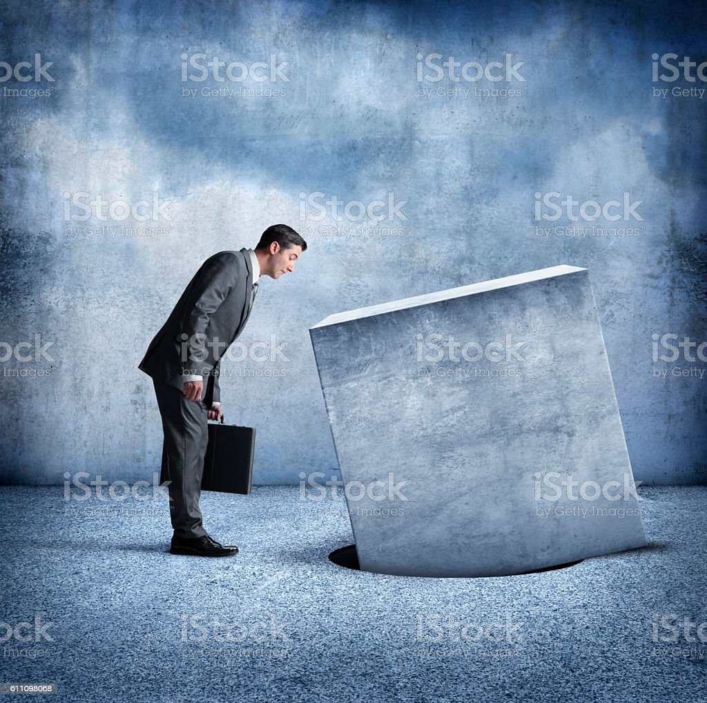 Businessman Looking At Square Peg Not Fitting Into Round Hole stock photo