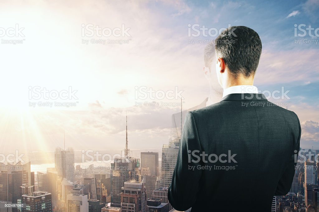 Businessman looking at sunrise from the top of building stock photo