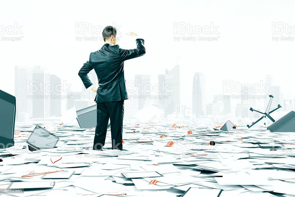 Businessman looking at the horizon among office stuff chaos stock photo