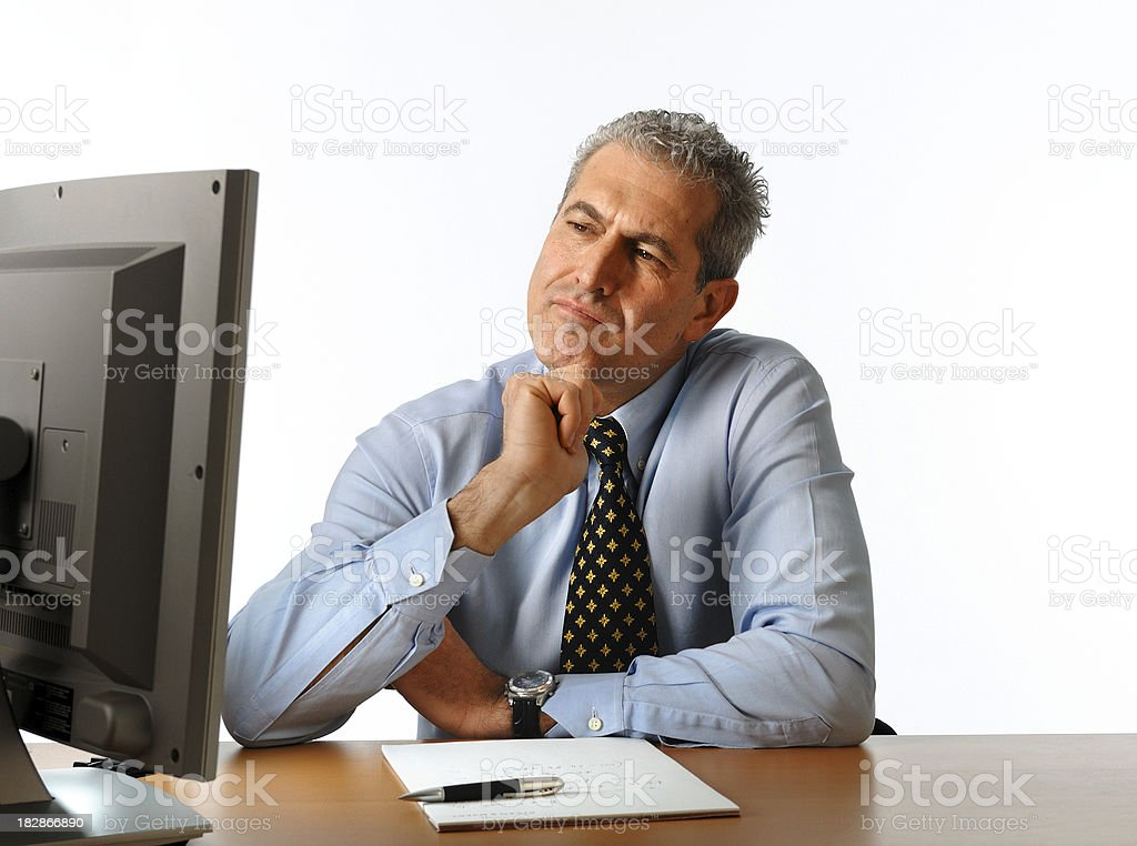 Businessman looking at the monitor touching his chin doubtfully royalty-free stock photo
