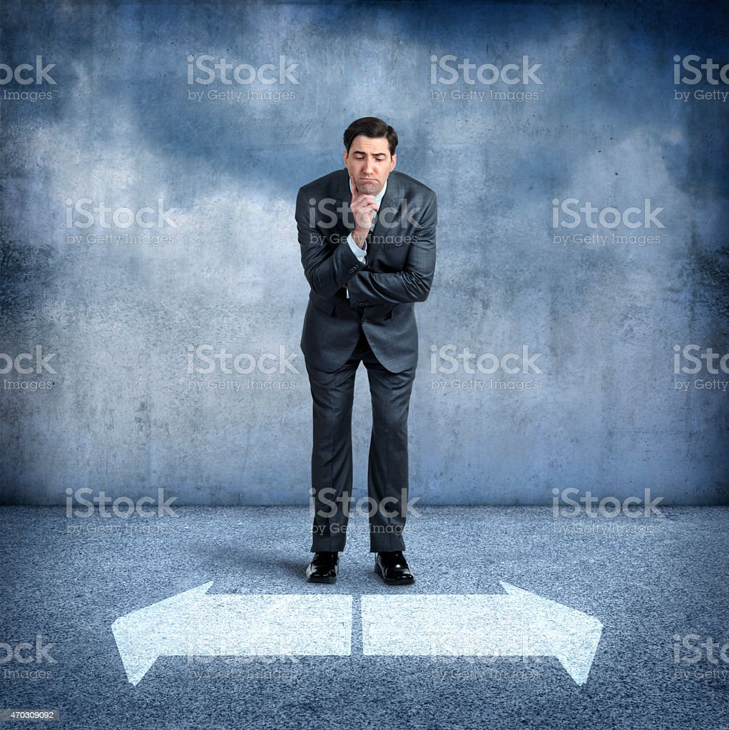 A businessman, standing with his hand under his chin and slightly...