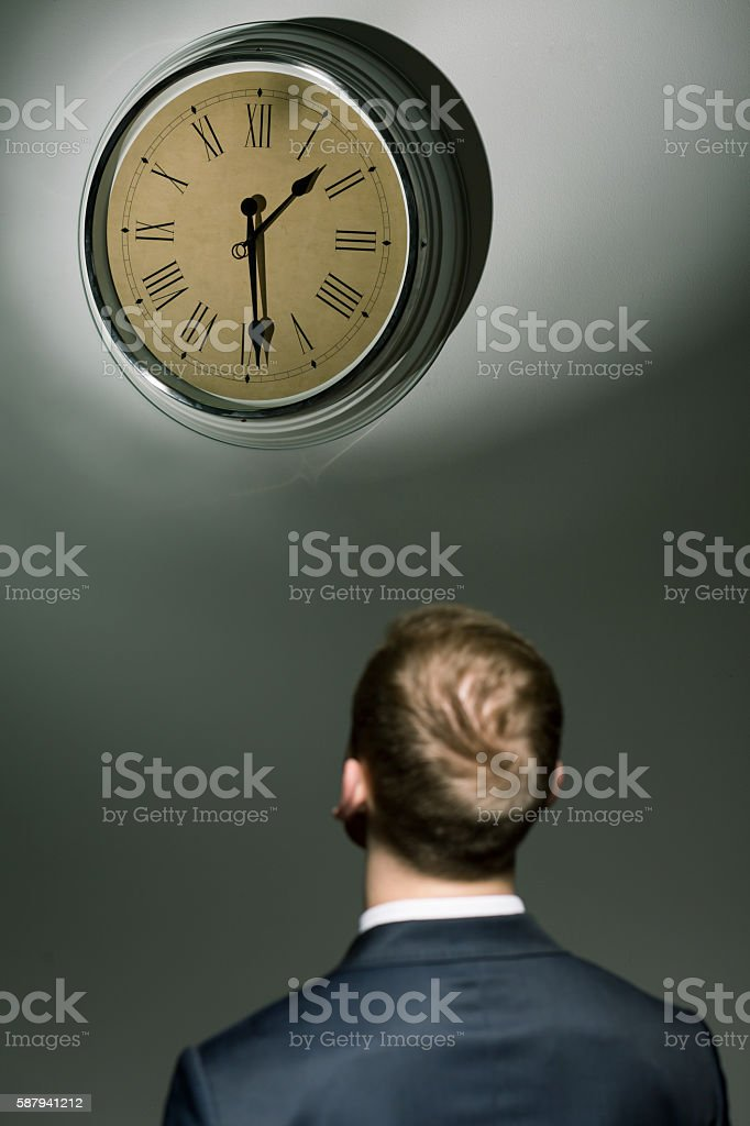 Businessman looking at watch with passing time stock photo