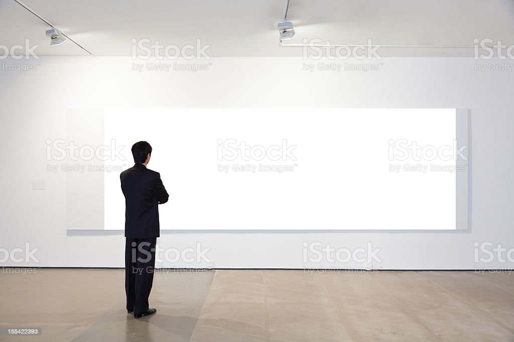Businessman looking at white frames in an art gallery stock photo