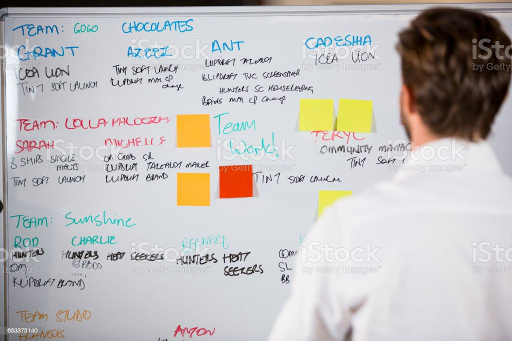 Businessman looking at whiteboard in office stock photo