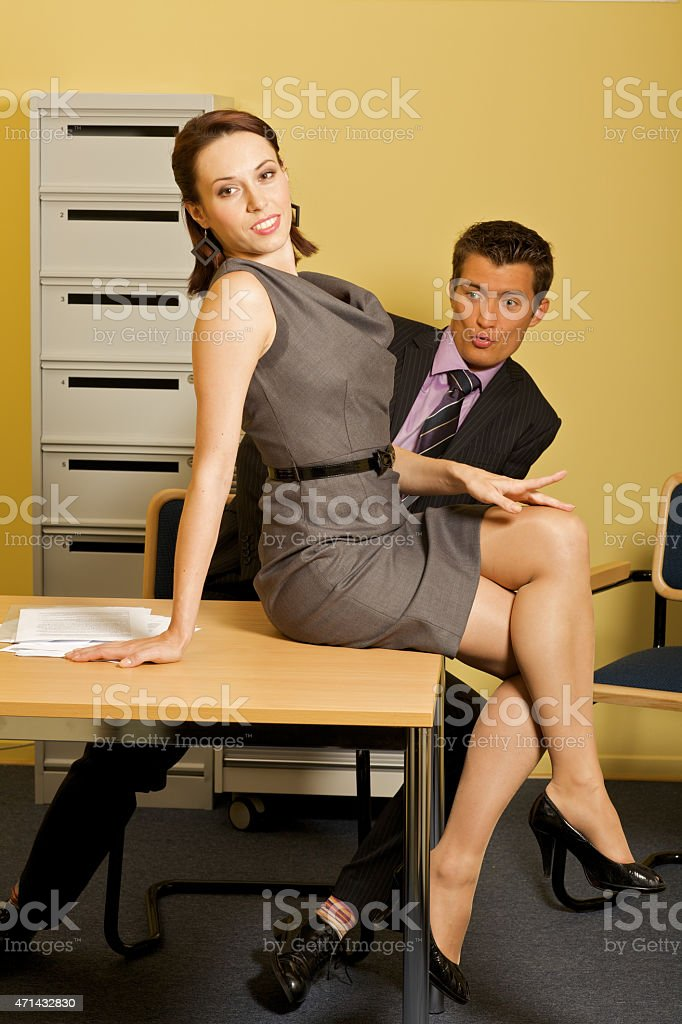 Businessman looking at woman sitting on table at office stock photo