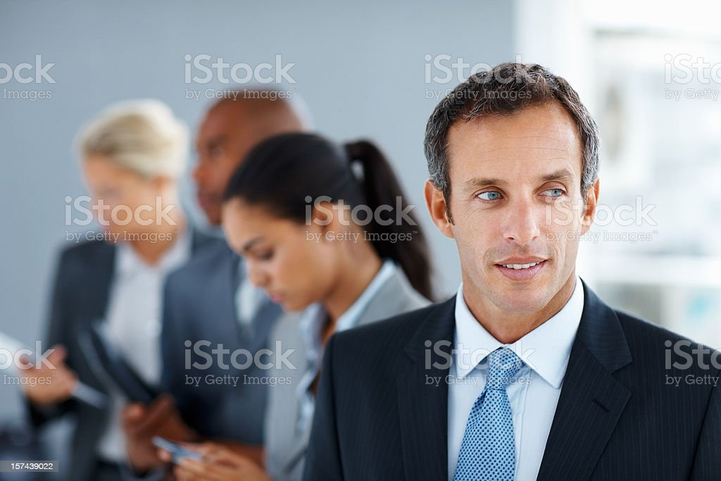 Businessman looking away with colleagues in the background royalty-free stock photo