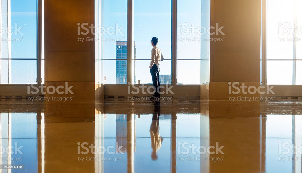 Businessman looking city through the window stock photo