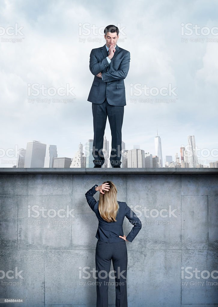 Businessman Looking Down At Businesswoman stock photo