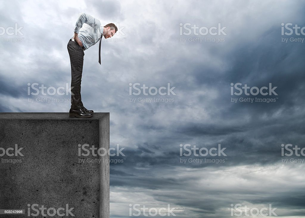 Businessman looking down on cliff stock photo