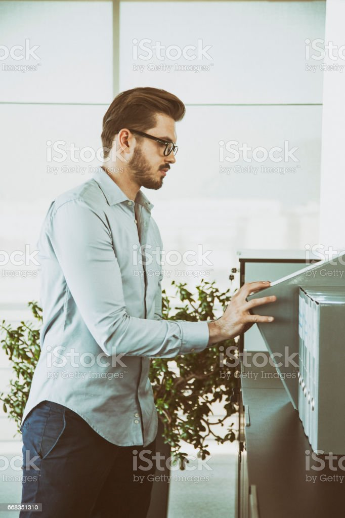 Businessman looking for the right ring binder stock photo