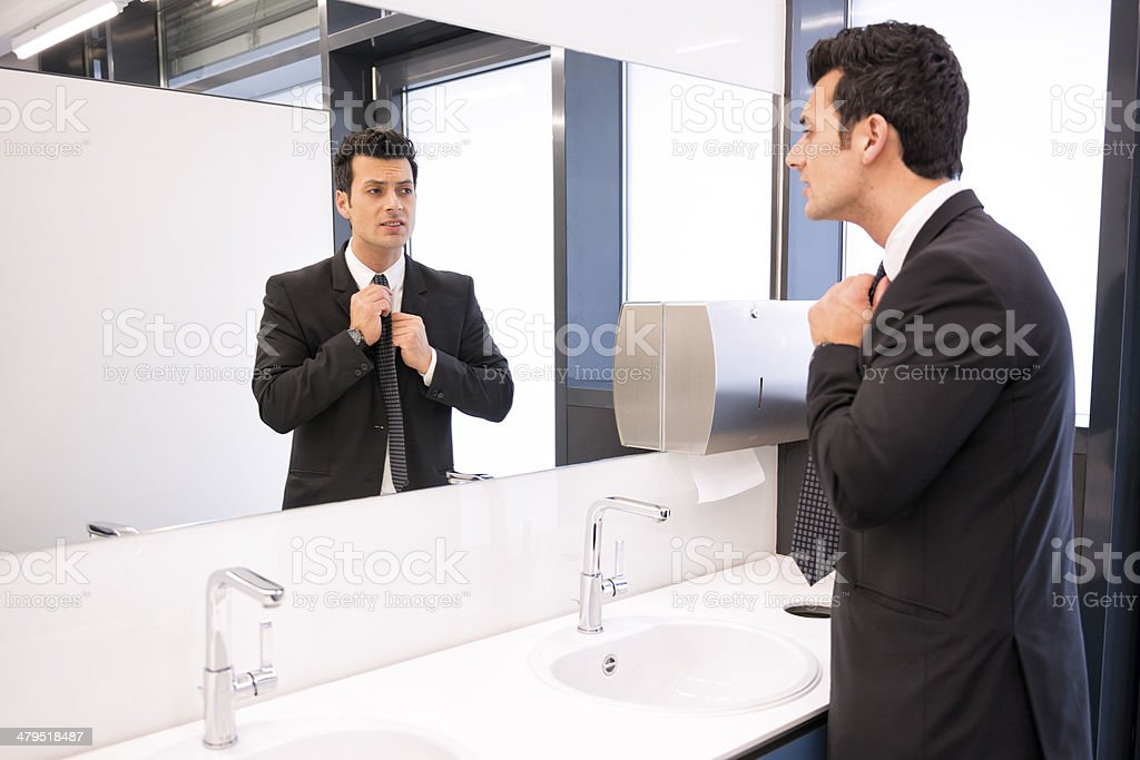 businessman looking into mirror at restroom stock photo