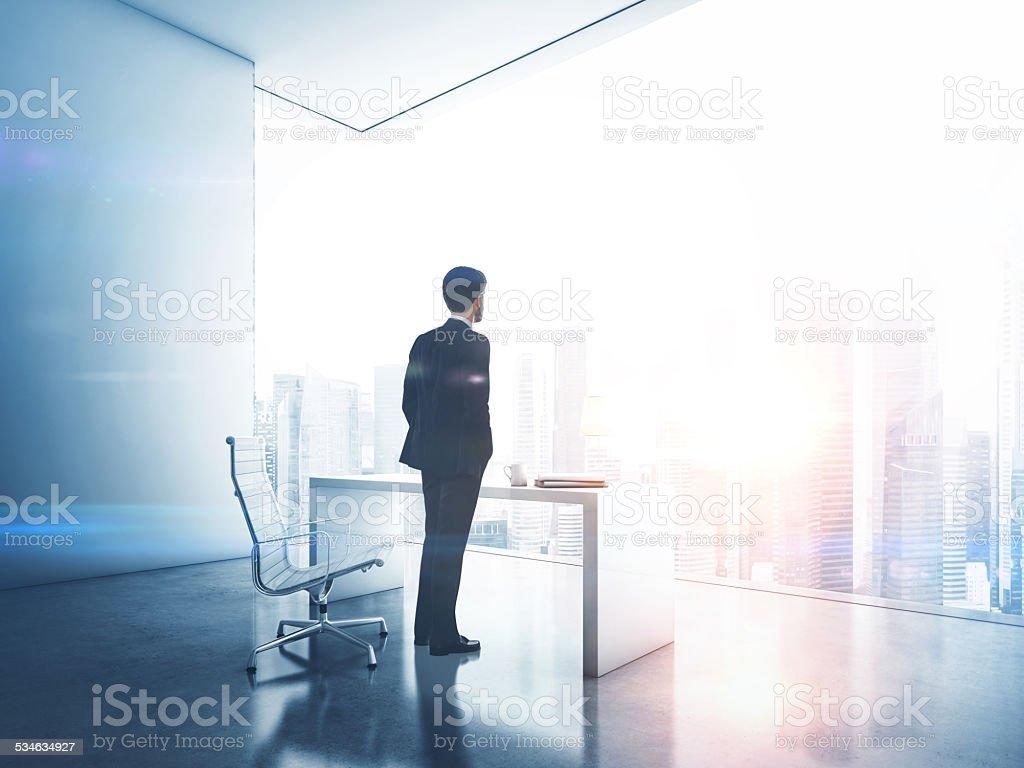 Businessman looking megalopolis through window stock photo