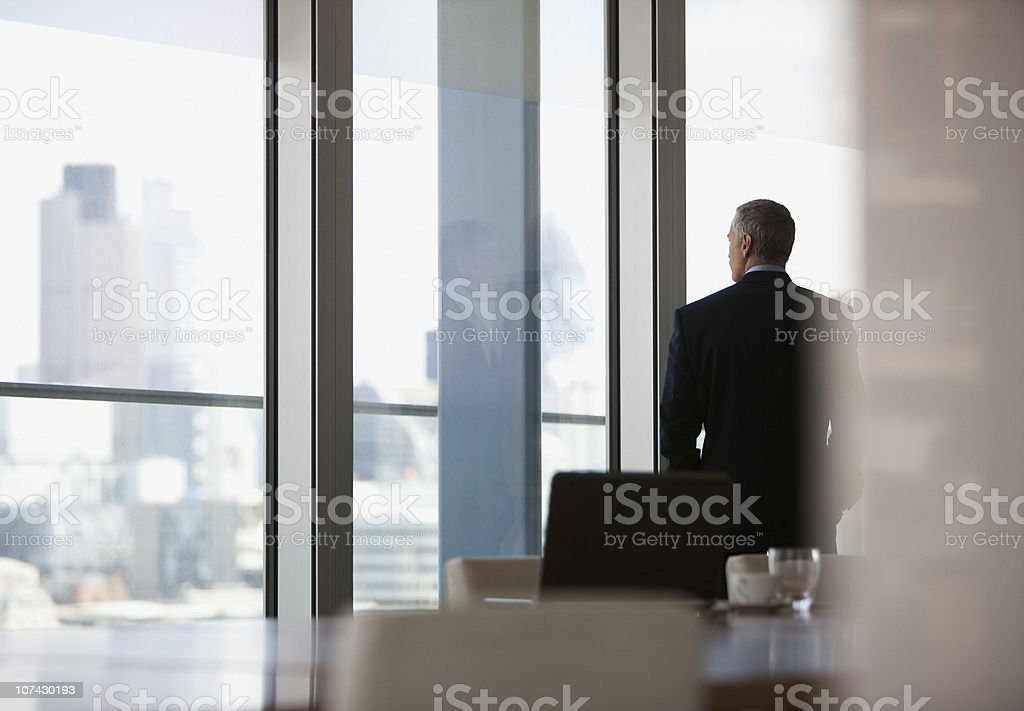 Businessman looking out conference room window stock photo