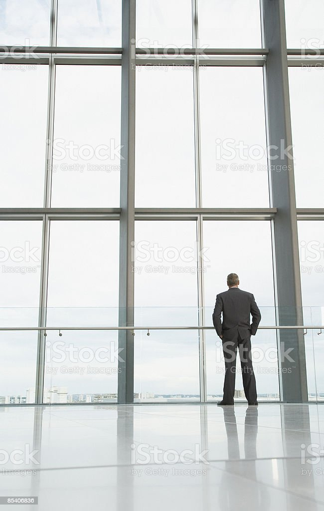 Businessman looking out lobby window stock photo
