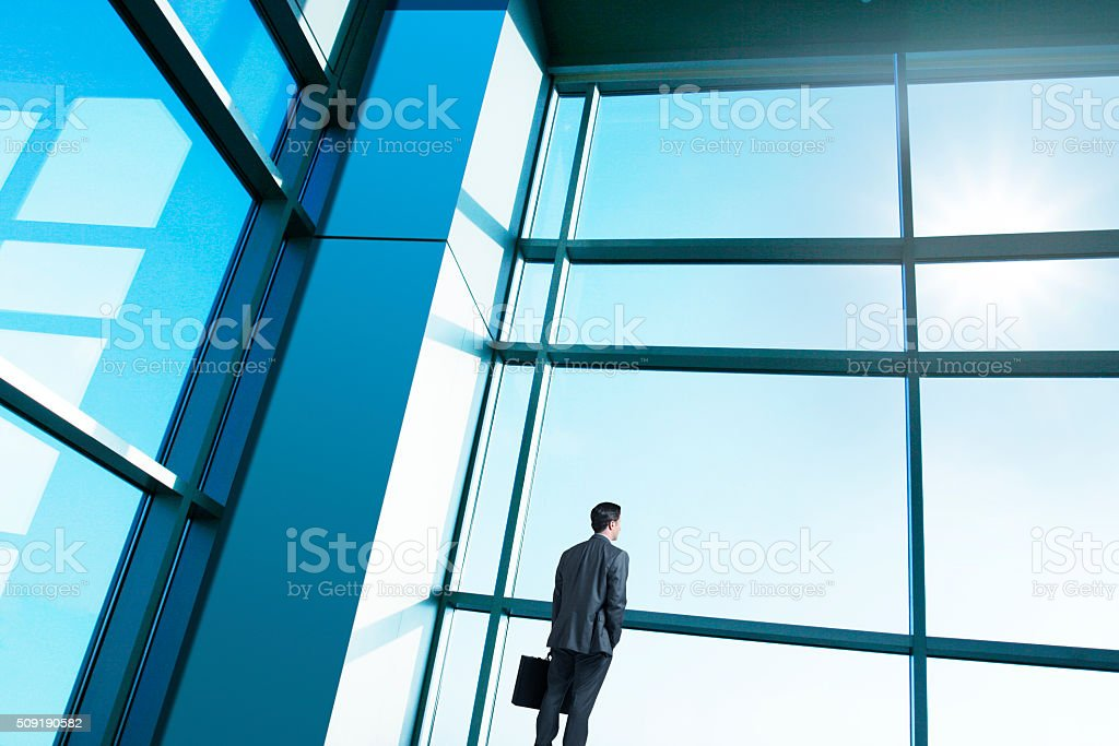 Businessman Looking Out Of Large Office Building Windows stock photo