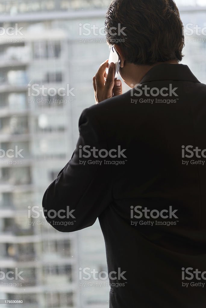 Businessman Looking Out of Office Tower while Talking on Phone royalty-free stock photo