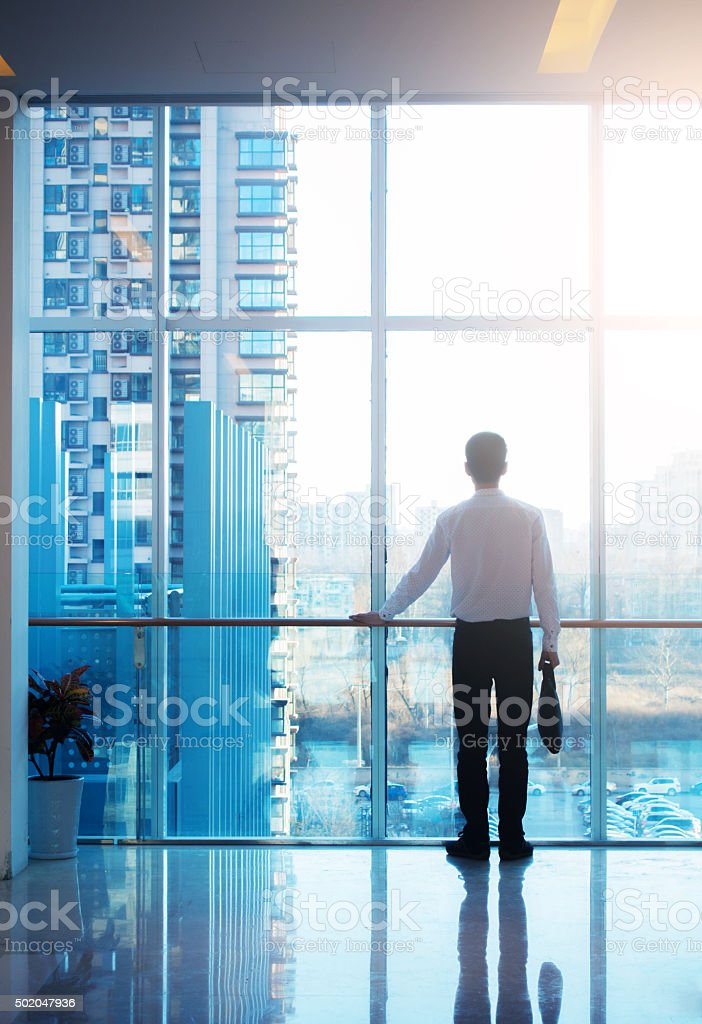 Businessman looking out of the window stock photo