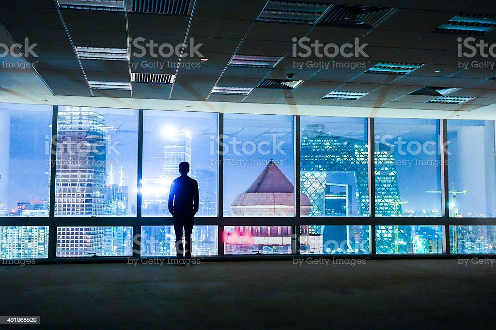 Businessman looking out of window stock photo