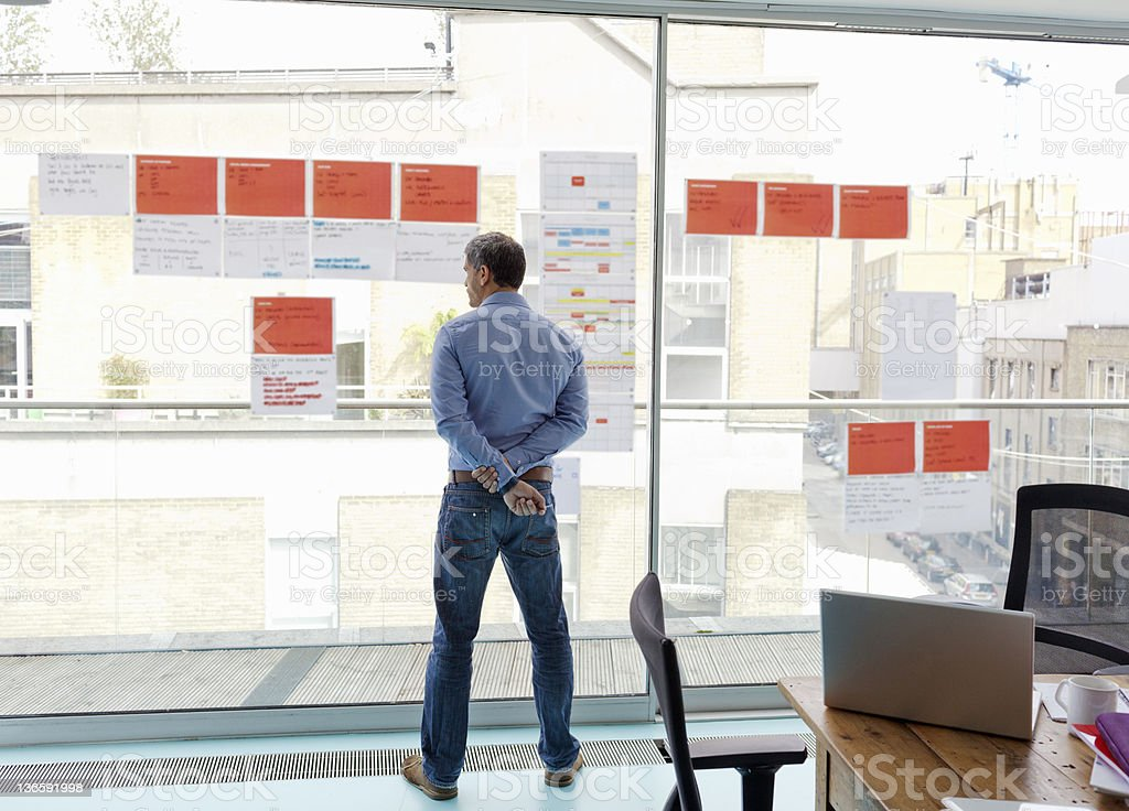 Businessman looking out office window royalty-free stock photo