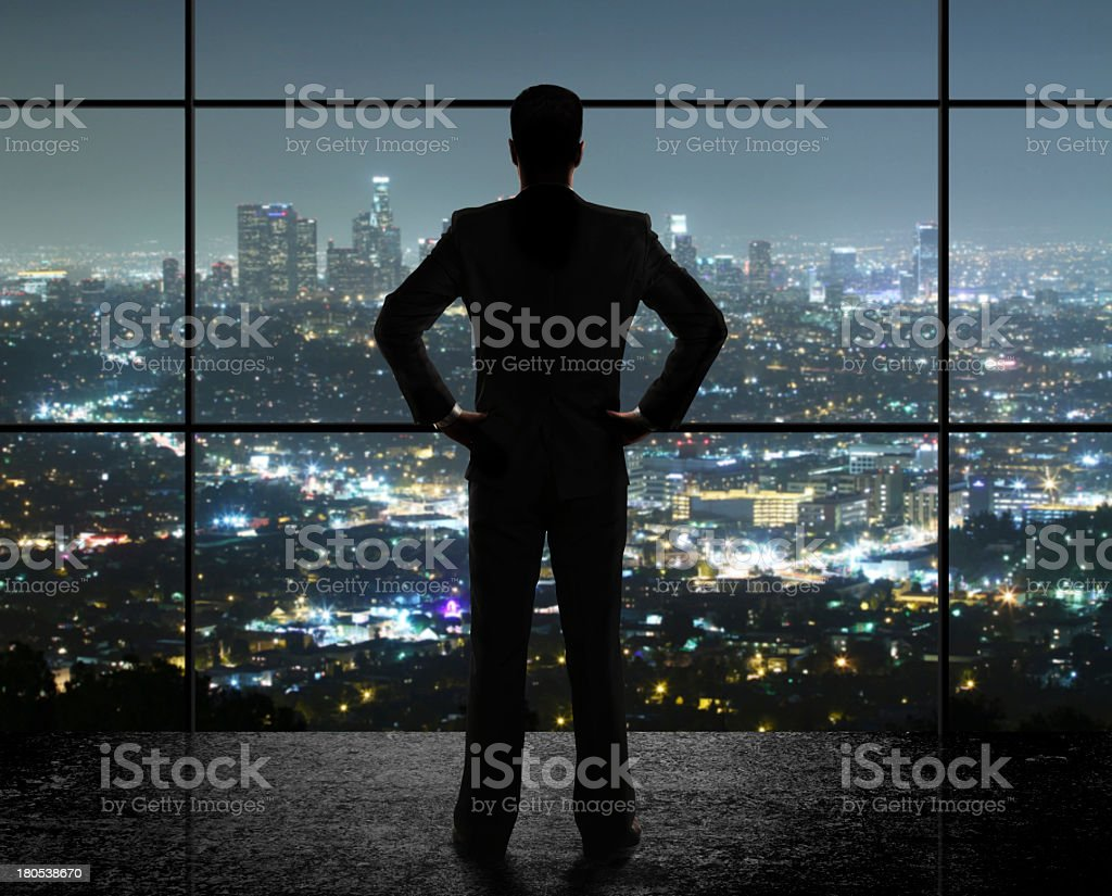 A businessman looking out the window at the night city royalty-free stock photo