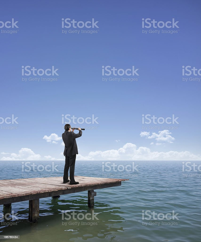 Businessman looking out to sea with a telescope stock photo