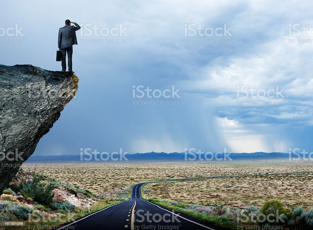 Businessman Looking Out Towards Long Lonely Desrt Highway stock photo