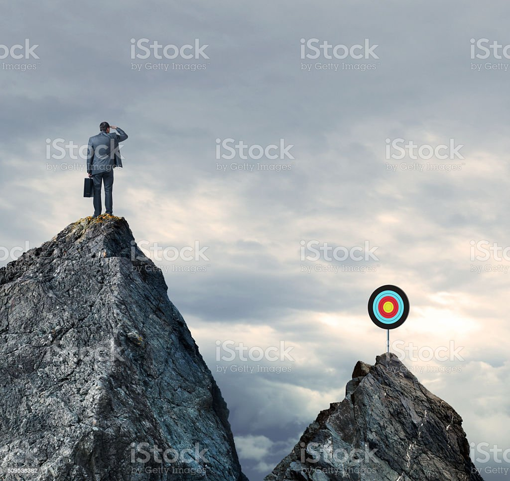 Businessman Looking Out Towards Target On Mountain Top stock photo