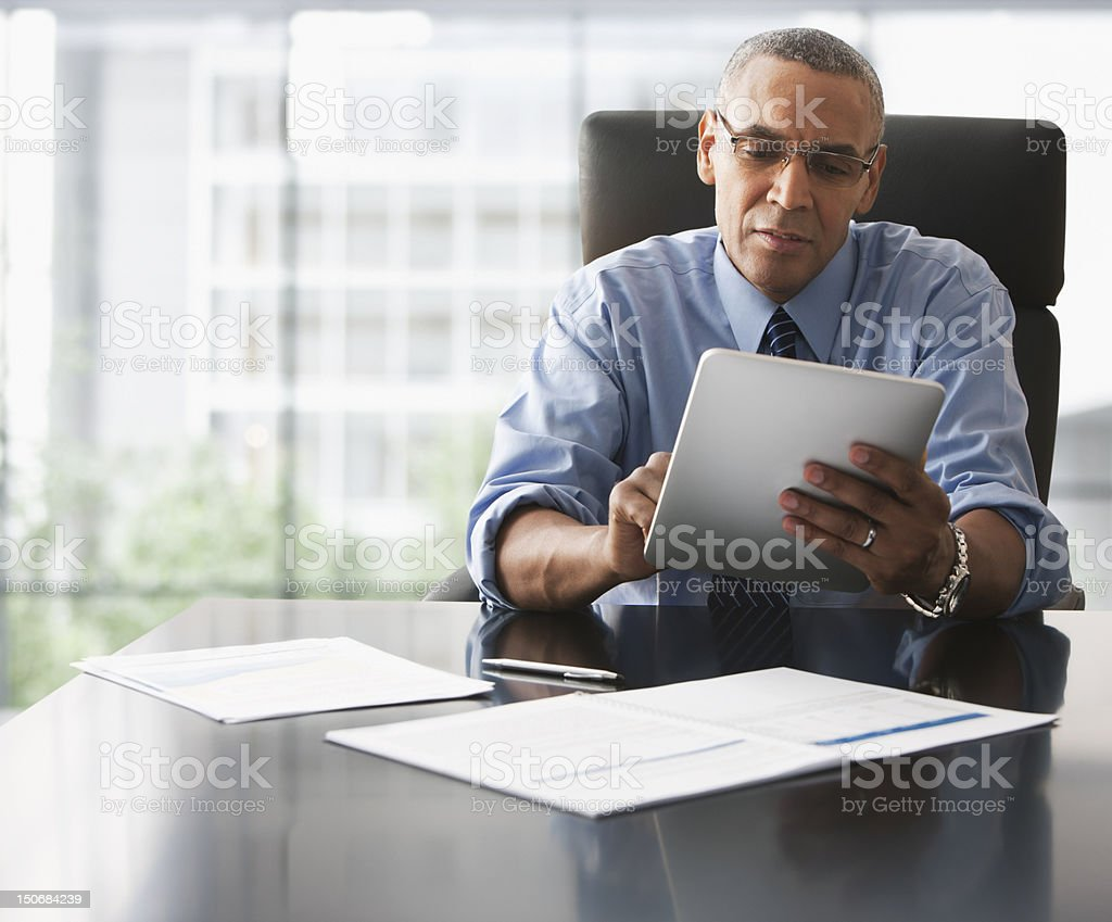 Businessman looking over electronic tablet stock photo