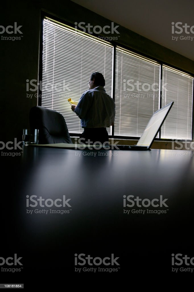 Businessman Looking Over Notes in Dark Office royalty-free stock photo