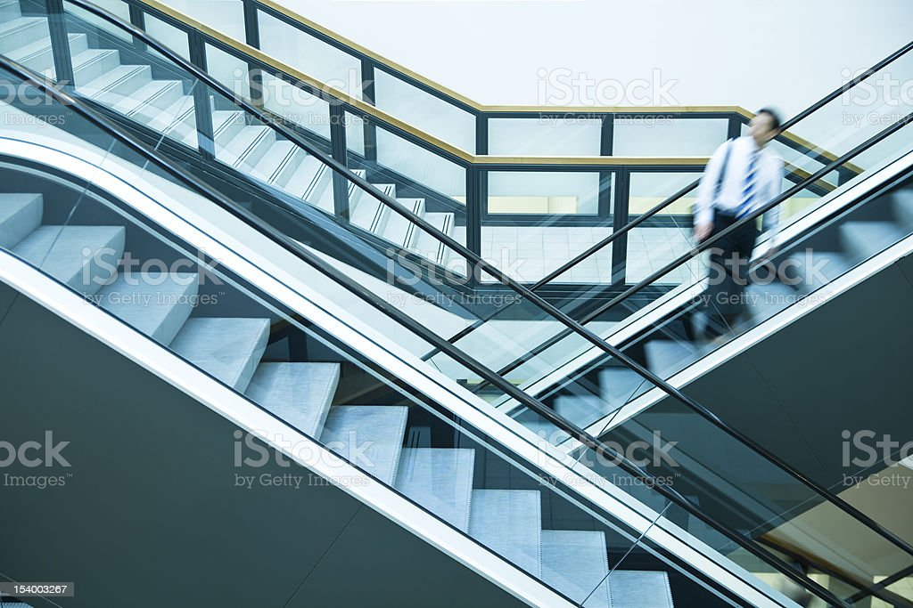 Businessman Looking over Shoulder on Escalator, Blurred Motion royalty-free stock photo
