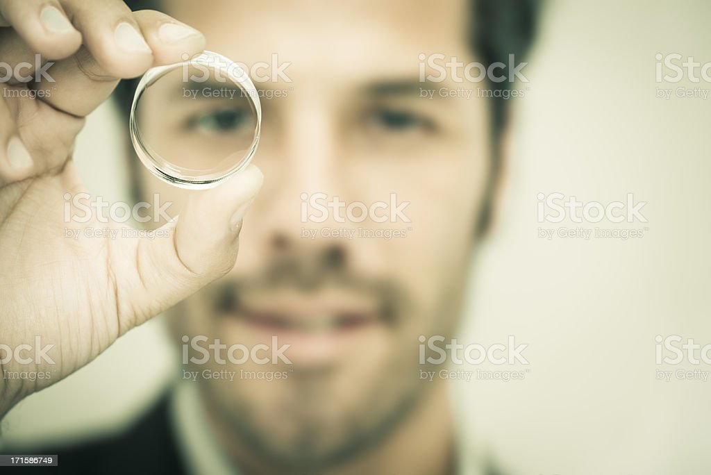 Businessman looking through a round lens stock photo