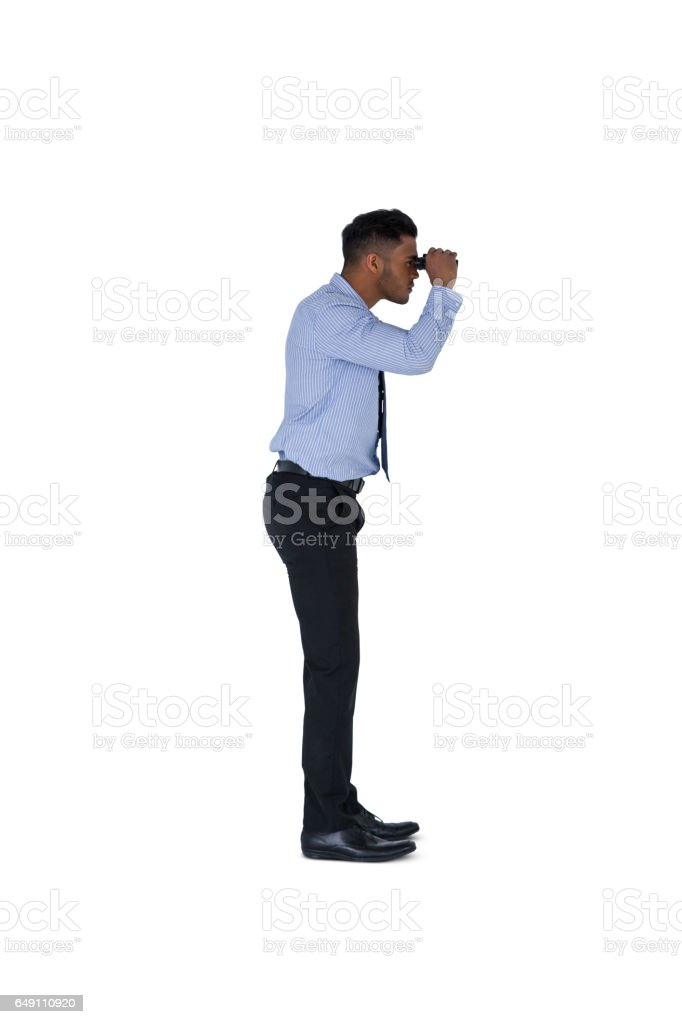 Businessman looking through binoculars against a white background stock photo