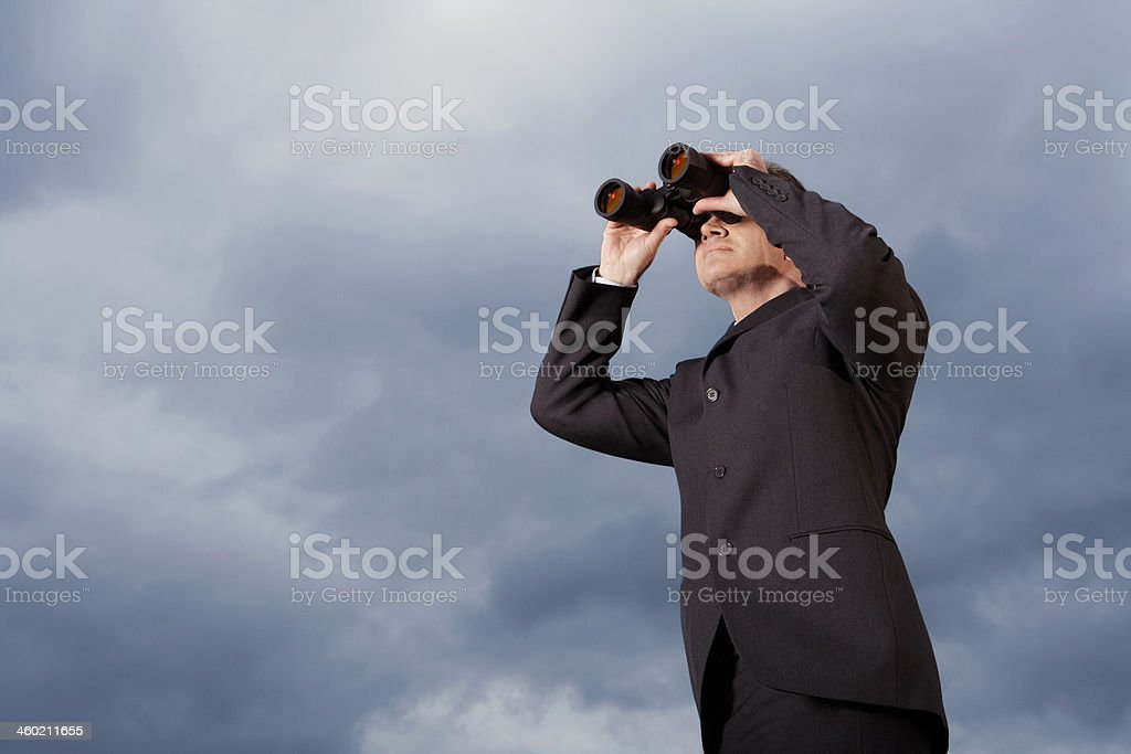 Businessman Looking Through Binoculars Against Sky royalty-free stock photo