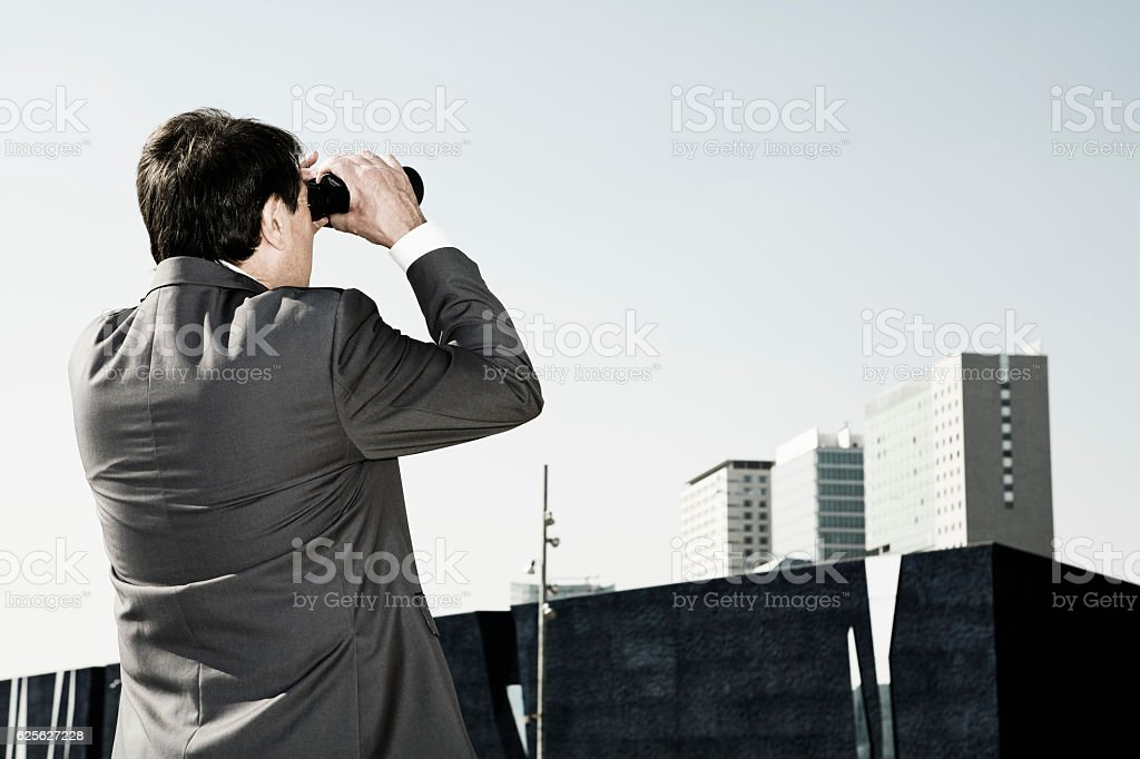 Businessman looking through binoculars at building stock photo