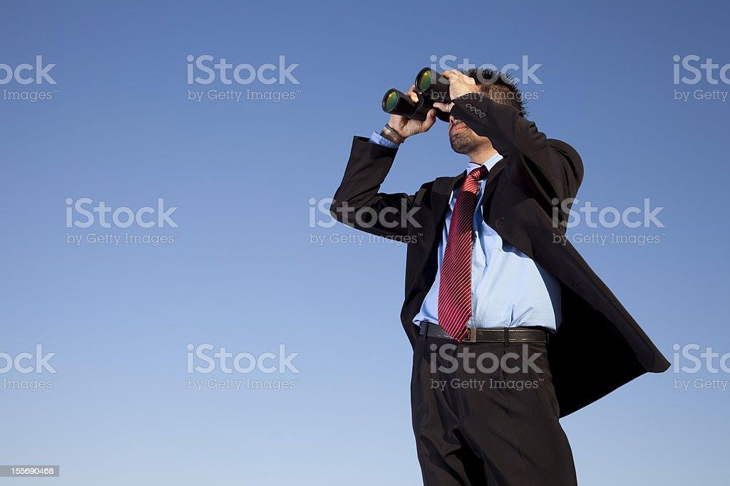 Businessman looking through binoculars stock photo