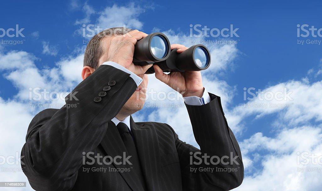 A businessman looking through binoculars stock photo