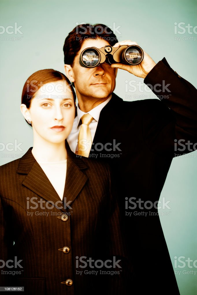 Businessman Looking Through Binoculars with Woman Standing Beside Him royalty-free stock photo