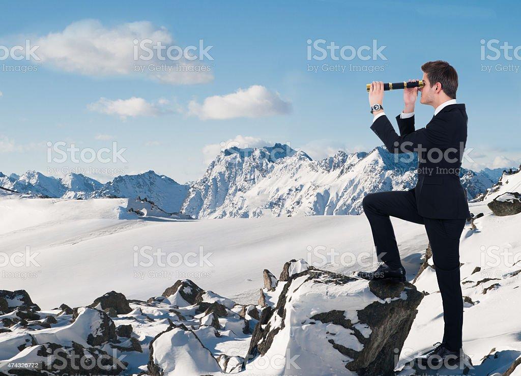 Hombre de negocios mirando a través del telescopio portátil en la nieve - foto de stock