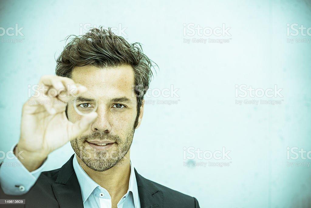 Businessman looking through lens stock photo