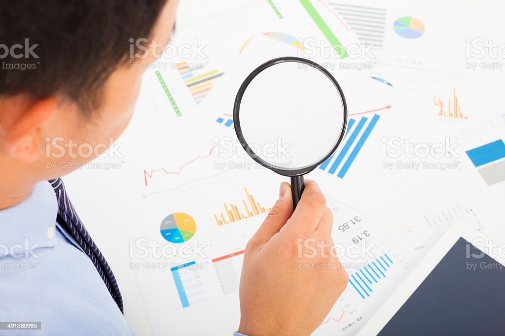 Businessman looking through magnifier glass to documents stock photo