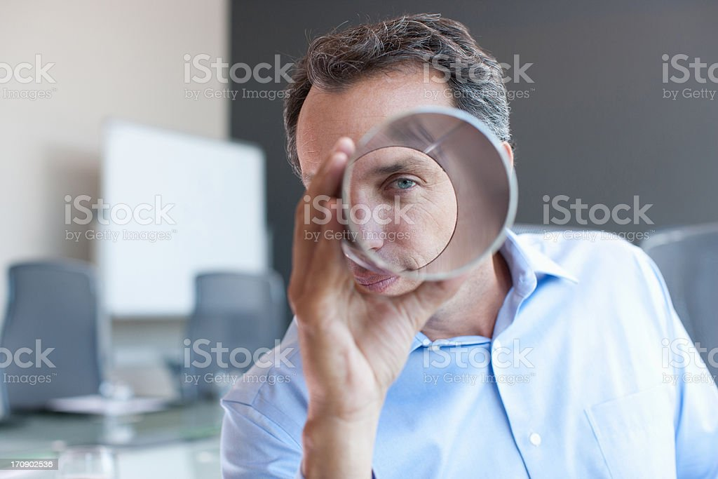 Businessman looking through metal cylinder in office stock photo