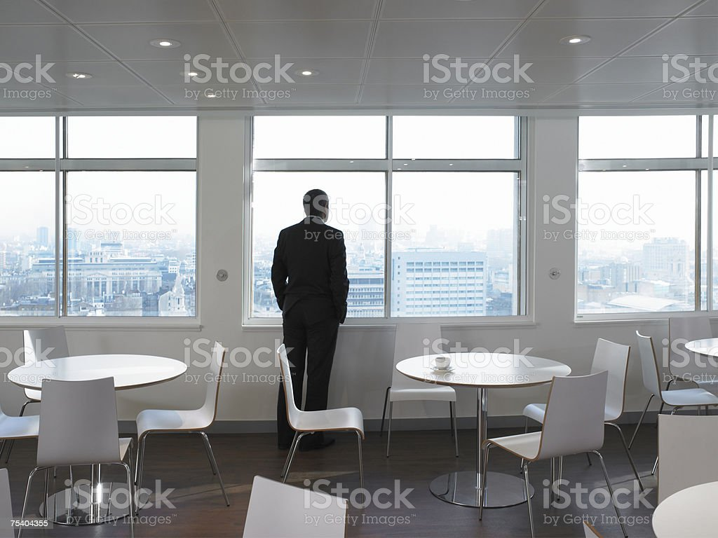 Businessman looking through window royalty-free stock photo